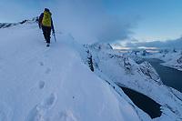 Female hiker on winter ascent of Reinebringen, Moskenesøy, Lofoten Islands, Norway