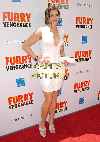 "BROOKE SHIELDS .at the Summit Entertainment L.A. Premiere of ""Furry Vengeance"" held at The Bruin Theatre in Westwood, California, USA, April 18th 2010..full length sleeveless white dress hand on hip open toe sandals scallop edge edged low cut clutch bag bracelet    silver   wavy trim   low cut red                                              .CAP/RKE/DVS.©DVS/RockinExposures/Capital Pictures."