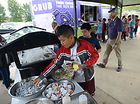 NWA Democrat-Gazette/ANDY SHUPE<br /> Kevin Castrellon, 10, a fifth-grader at Holt Middle School, picks out toppings for his lunch Wednesday, Oct. 10, 2018, outside the district food truck as principal Matt Morningstar (right) speaks with students at Holt Middle School in Fayetteville. The food truck made its first stop in a tour of Fayetteville Public School's secondary schools in the Food Truck Dayz lunch series to raise awareness for the truck and the service it provides to promote healthy eating habits and offer meals to students in need.