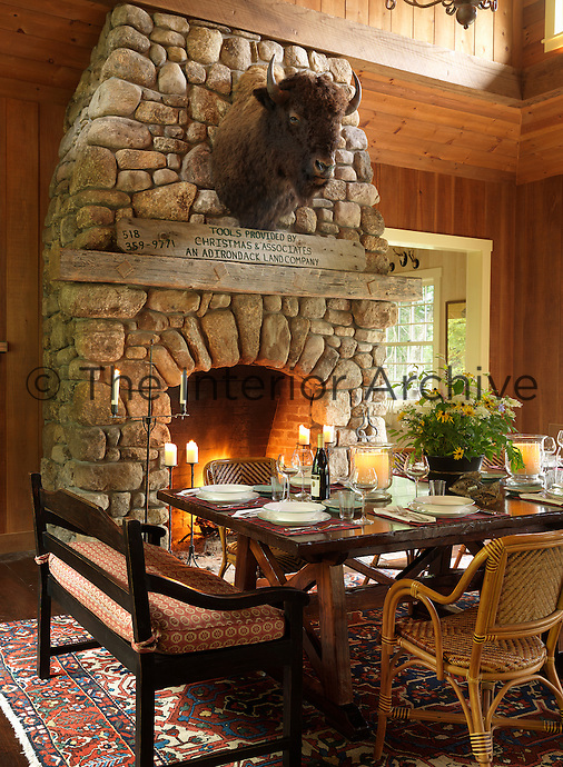 A large buffalo head looks down from the stone chimney breast onto the dining table