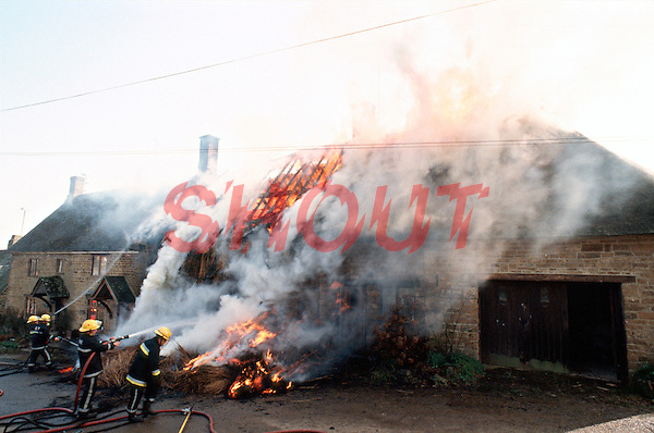 Firefighters attending a thatched house on fire. The fire has spread through the thatched roof and is spreading from one property to another. They are using many hoses to try and slow down the spread of the fire. This image may only be used to portray the subject in a positive manner..©shoutpictures.com..john@shoutpictures.com