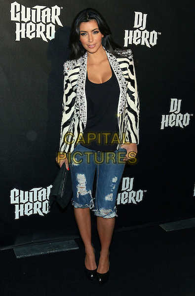 KIM KARDASHIAN.DJ Hero Launch held at the Wiltern Theatre, Los Angeles, California, USA..June 1st, 2009.full length collar striped stripes zebra animal print top cleavage black white beads beaded jewel encrusted embellished jeans denim cropped ripped torn clutch bag .CAP/ADM/TC.©T. Conrad/AdMedia/Capital Pictures.