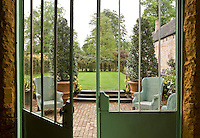 A view through the elegant glass and metal doors of the orangery to the terrace beyond