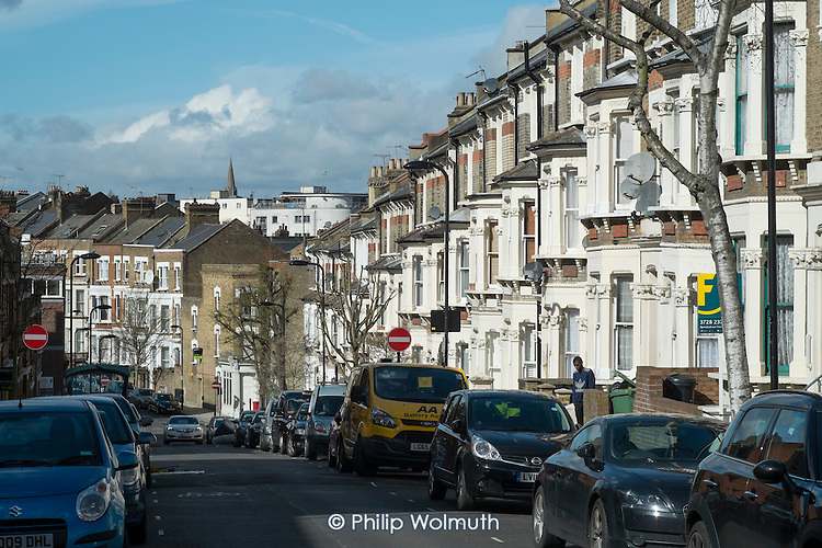 Parked cars and Victorian terraced housing, West Hampstead, London.
