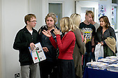 Staff member (in red) giving advice, Open Day at Kingston College when prospective students and their parents look around.
