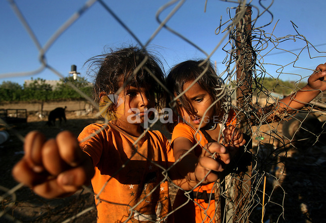 Palestinian girls play outside their house in the Khan Yunis camp in the southern Gaza Strip June 15, 2013. Photo by Eyad Al Baba