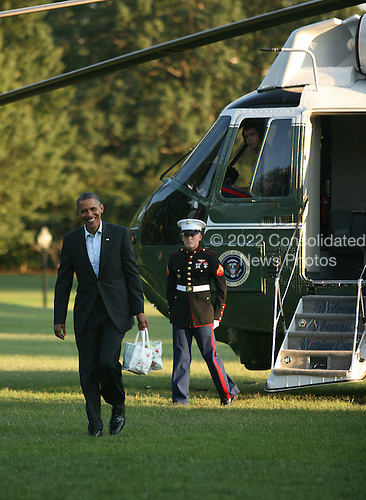 United States President Barack Obama returns to the South Lawn of the White House from a day of campaigning in New Hampshire, carrying a bag of green apples and a caramel apple making kit from Mack's Apples in Londonderry, New Hampshire,  August 18, 2012..Credit: Martin Simon / Pool via CNP