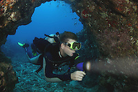 This diver (MR) with dive light on is swimming into an underwater cavern. Hawaii.