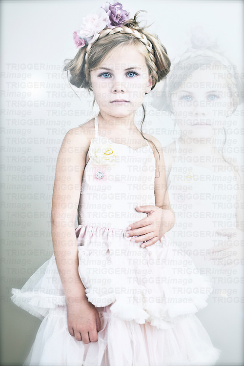Young girl with blonde hair in a plait wearing white party dress