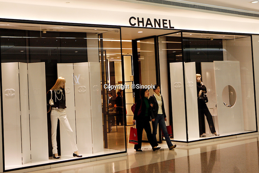 People coming out from a Chanel store in Shanghai, China. Chanel and many other top-end designers are expanding into China despite the proliferation of fakes easily available..13 Mar 2006