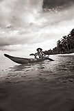 INDONESIA, Mentawai Islands, Kandui Resort, fisherman Gesayas Ges paddling his dugout canoe (B&W)
