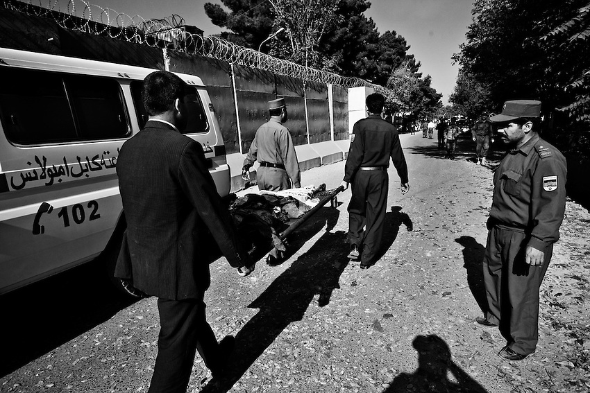 Afghan Police and hospital workers carry the body of a girl killed by a suicide bomb in Kabul, Afghanistan, Thursday, Oct 8, 2009. The bomb exploded at approximately 8:37 a.m. near the Indian Embassy and Afghan Interior Ministry office, killing at least 12 people. Two UN vehicles were also hit in the attack.