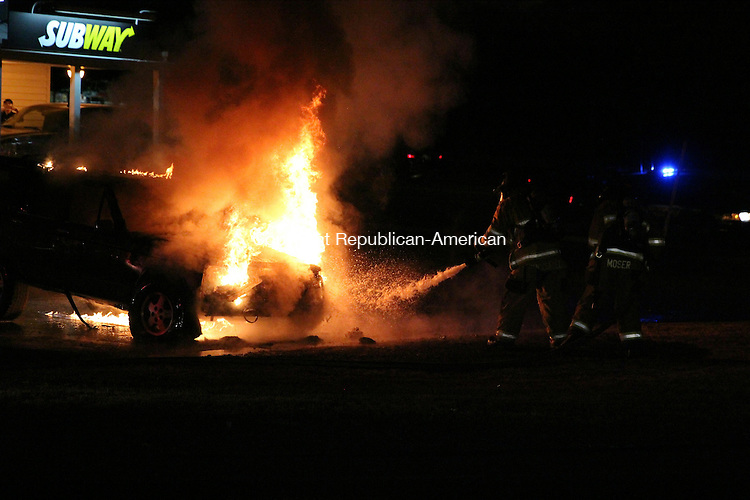 SOUTHBURY, CT: 10 Dec. 2015: 10122015CB03: SOUTHBURY -- Firefighters battle a vehicle blaze Thursday in Southbury at the Subway parking lot on Oak Tree Road near the intersection of Main Street South. Caleb Bedillion Republican-American