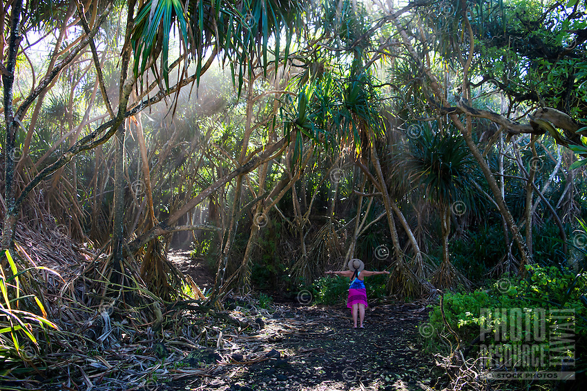 A woman in a hat and beachwear opens her arms as the sun filters through trees in the Kapoho area of Puna, Hawai'i Island.