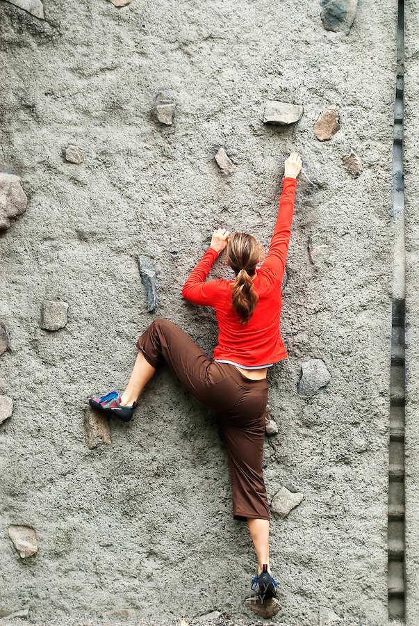 Female rock climber in red shirt climbing at University of Washington practice climbing wall, Seattle WA.