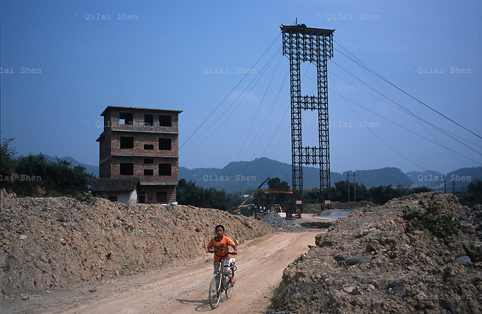 A boy rides a bicycle near a temporary bridge erected at an highway construction site near Guilin, Guangxi Province, China on 19 October, 2008.  China has undergone a major road building project as an investment in basic infrastructure and a cornerstone in economic development, linking cities by highways and vowing to extend its road network to every village in the country. More than 33,000 kilometers (20,500 miles) of highways have been built in the last five (5) years and China is on track to top the U.S. in terms of roadways...