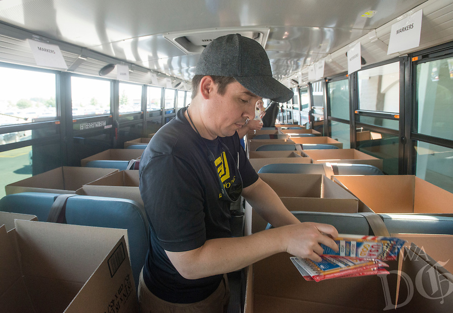 NWA Democrat-Gazette/BEN GOFF @NWABENGOFF<br /> Lucas Finch sorts supplies while volunteering with other employees from Ernst & Young in Rogers Friday, Aug. 3, 2018, at the United Way of Northwest Arkansas Fill the Bus drop-off location at the Walmart Supercenter on Pleasant Crossing Boulevard in Rogers. Volunteers are manning busses at ten Walmart Supercenter locations in Northwest Arkansas and Pineville, Mo. from 9:00 a.m. to 3:30 p.m. Friday and Saturday to sort donated school supplies. The donations will go directly to the district the Walmart location is in. Over the past ten years, the annual drive has helped more than 35,000 students in 12 school districts get the supplies they need to start the school year.