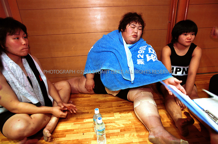 10/26/2001--Hirosaki, Aomori Prefecture, Japan..Rie Tsuihiji (center) rests after completing the final round of the team event at the world sumo championships. ..Photograph by Stuart Isett/Gamma.©2002 Stuart Isett