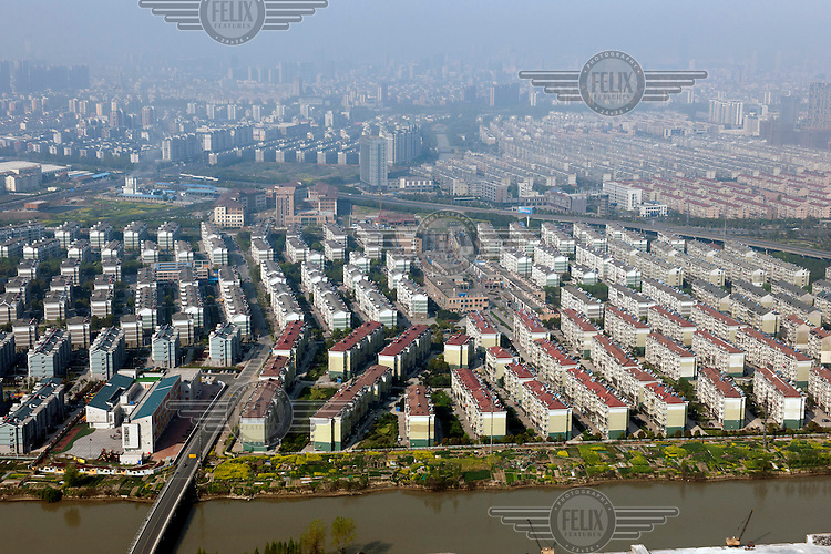 Row after row of newly built housing blocks. The city in the distance is partially obscured by smog. /Felix Features