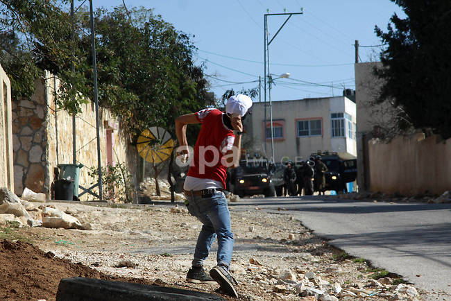 A Palestinian protester throws stones towards Israeli security forces as clashes broke out during a demonstration against the expropriation of Palestinian land by Israel in the village of Kfar Qaddum, near the occupied West Bank city of Nablus, on Dec. 27, 2013. According to reports, ten Palestinians were reportedly wounded during the clashes accompanying the weekly Friday demonstrations of Palestinians against Jewish settlements. The number of wounded Israeli soldiers was not immediately known27, 2013. Photo by Nedal Eshtayah