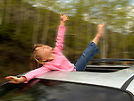 Child playing in car roof.  Vail, Colorado.