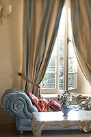 In one of the eight hotel bedrooms a comfortable chaise longue is strategically placed under a window