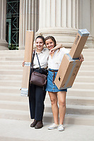 Young women pose with home-made eclipse viewers on the steps outside of MIT's Building 7 on Massachusetts Avenue on the campus of MIT after a solar eclipse viewing event in Cambridge, Massachusetts, USA, on Mon., Aug. 21, 2017. This solar eclipse is the first in nearly 40 years to have a path observable total eclipse from coast to coast in the United States. People at this location in Massachusetts, however, only observed about 66% coverage of the moon over the sun.