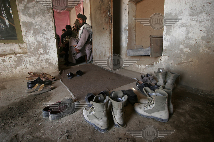 Boots and shoes left outside a room where Norwegian ISAF troops meet with local leaders.  ISAF, the International Security Assistance Force, is a peacekeeping mission affiliated to the United Nations (UN) and NATO. Tradition and respect. Kabul, Afghanistan.