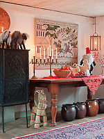 Warm candlelight illuminates a textile print on the dining room wall