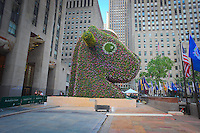 "Jeff Koons' sculpture ""Split-Rocker"" is readied for its debut in Rockefeller Plaza in New York on Sunday, June 22, 2014. The 37-foot high topiary sculpture consisting of over 50,000 flowering plants will officially open to the public on June 25 and be on display until September 12. The exhibit coincides with a retrospective of Koon's work at the Whitney Museum of American Art. (© Richard B. Levine)"