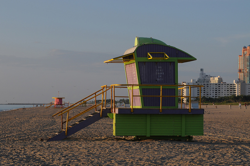 Quiet early morning at Miami Beach, South Beach, a few people up and enjoying the Sunrise, near the Pink and green lifeguaurd huts.