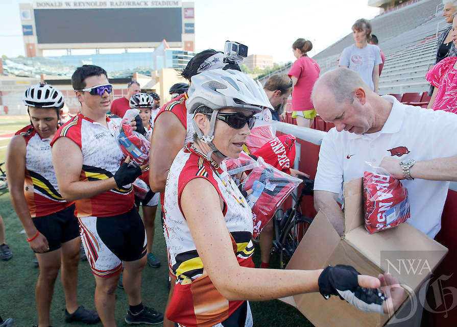 NWA Democrat-Gazette/DAVID GOTTSCHALK   Matt Trantham, senior associate athletic director at the University of Arkansas, (right) helps distribute Razorback cycling jerseys Wednesday, June, 22, 2016, with Marisa Cabe, of Cherokee, NC., to a group of riders participating in the Remember the Removal Bike Ride at Donald W. Reynolds Razorback Stadium in Fayetteville. Stacy Leeds, dean of the University of Arkansas School of Law, a citizen of the Cherokee Nation, is participating in the annual trek from North Carolina to Tahlequah. The ride, which ends today (Thursday), commemorates the Trail of Tears, when in 1838 the Cherokee nation was forced to give up its lands east of the Mississippi River and to migrate to an area in present-day Oklahoma.