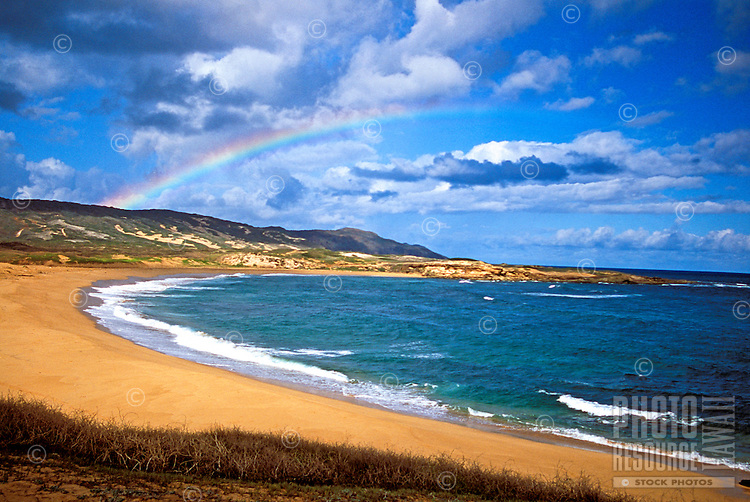 Lovely Kepuhi beach on Molokai's west end with a shimmering rainbow in the distance.