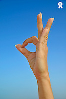 Woman making 'OK' hand sign on blue sky (Licence this image exclusively with Getty: http://www.gettyimages.com/detail/103301317 )