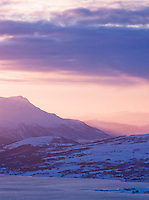 Sunset colours the landscape across the mountains, seen from Mount Storsteinen at Tromso, Norway