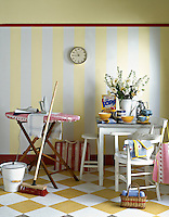 A domestic scene with breakfast items on a white painted table. A broom is propped up against an ironing board and a bucket stands nearby.