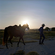 Cowboy Church. Texas, USA. 2007. A parishioner of the church walks his horse at sunset just before roping night at the cowboy church.
