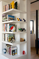 A collection of miniature designer chairs is displayed on open shelving in the living area