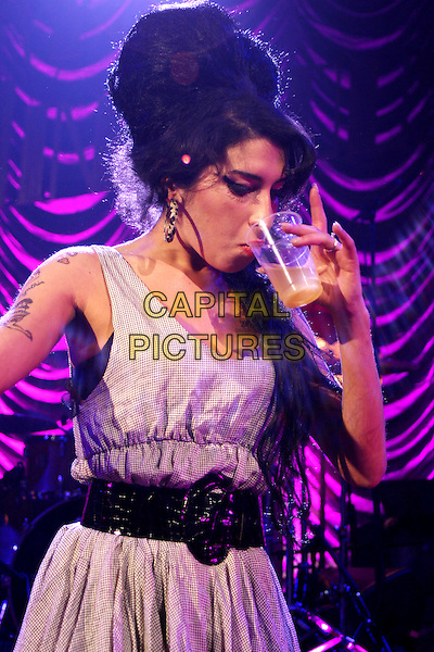AMY WINEHOUSE.Live in concert at the Shepherd's Bush Empire, London, England..May 28th, 2007.gig performance music half length grey gray dress back belt drink cup glass beverage tattoos drinking .CAP/MAR.© Martin Harris/Capital Pictures.