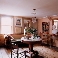 The upstairs parlour is furnished with a 19th century sofa, Hitchcock chairs and an antique pedestal table; a painting by Mary Hackett hangs above a framed sketch by illustrator Howard Chandler Christy