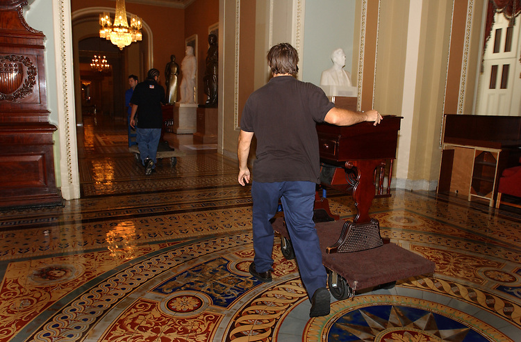 carpet2_080802 -- Workers move the desk from the floor of the Senate floor of the U.S. Capitol so new carpet can be installed.
