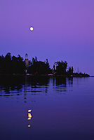 The Old Baileys Harbor Lighthouse sits in twilight as the moon rises over Lake Michigan