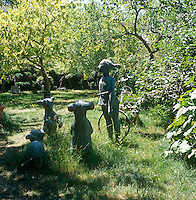 A secluded, naturalistic garden with long grass and a cherry tree. A group of stone figures stand by a path.
