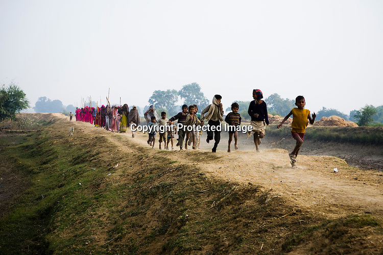 Children run win excitement as the 47-year-old leader of the Pink Gang, Sampat Pal Devi is seen coming from a distance. A fiesty woman. The barely educated, impoverished mother of five, Sampat Pal Devi has emerged as a messianic figure in the region. Sampath Devi began to work as a government health worker, but she quit soon after because her job was not satisfying enough. She always wanted to work for the poor and not for herself. Taking up issues while being a government worker was difficult, so she decided to quit the job and work for the rights of people...Amidst the gloom of extreme poverty, it's the colour of pink that's calling the shots in this dusty region of Bundelkhand, one of the poorest parts of one of India's northern and most populous states, Uttar Pradesh in India. A gang of vigilantes, called the Gulabi Gang (pink gang) - its 10,000 strong women members wear only pink sarees - is taking up lathi (traditional Indian cudgel) against domestic violence and corruption.