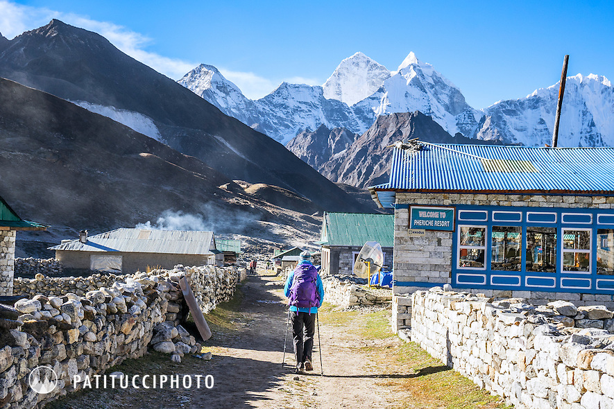 A lone trekker passes through the village of Pheriche in the Khumbu Valley, Nepal Himalaya.