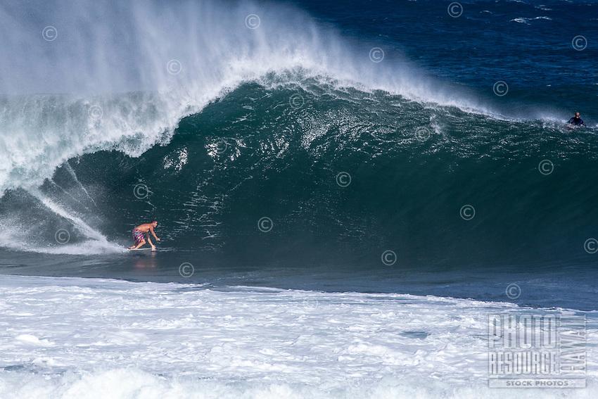 A surfer rides a big wave at Pipeline (off of 'Ehukai Beach Park), North Shore, O'ahu.