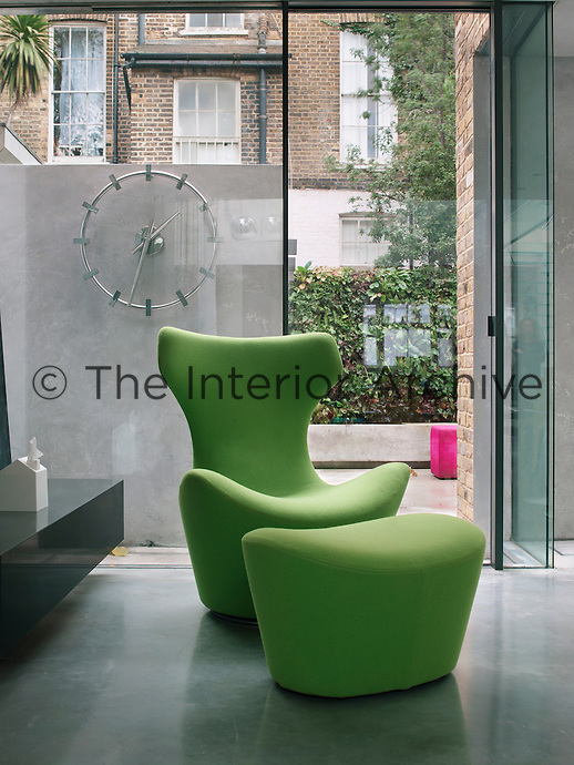 A green 'Grande Papilio' chair and matching foot stool, from B&B Italia, in the kitchen. An industrial steel clock ticks away behind them on a concrete wall in the garden