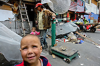 A Colombian recycler with his family waits in the 'Invasión', a temporary slum in Bogota, Colombia, 1 April 2006. The internal armed conflict in Colombia together with lack of social network caused appearence of small invasion slums in all Colombian urban zones in last years. These illegal settlements rise quickly in free uncontrolled spaces between industrial buildings, both in the city centres and peripheries. Shacks do not have sanitation network, neither electricity. Most of their inhabitants are war fugitives violently displaced from their original lands in the country by guerrilla or paramilitary forces. Picking up the rubbish and recycling it is a common survive strategy for people living in these temporal ghettos until those are not dismantled by city administration.