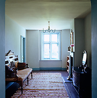 A Moroccan bench stands on this landing which has been painted in a blue limewash