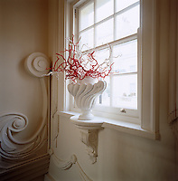 Close up of an elegant window sill with a round excess large enough to house a vase, here filled with red and white twigs